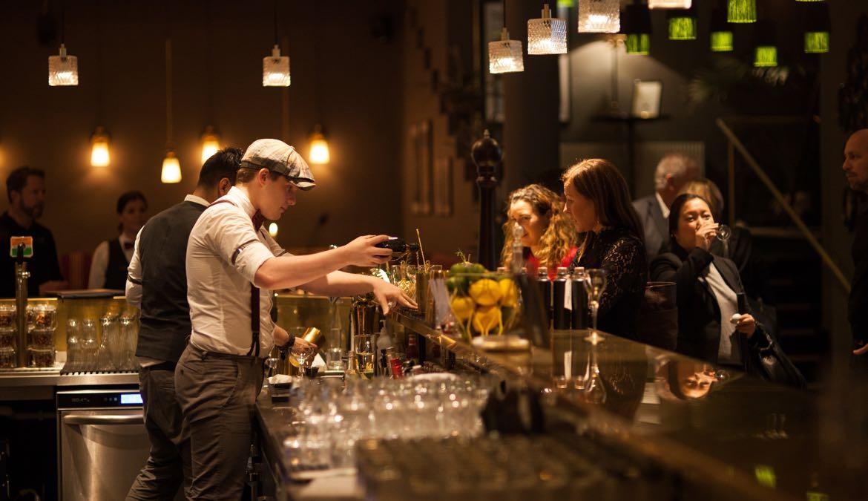 Bild på en bar, personer som blandar drinkar och beställer