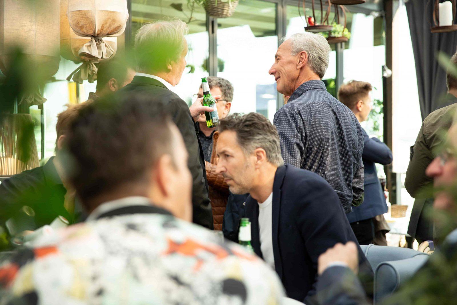 Två män står och pratar i en bar
