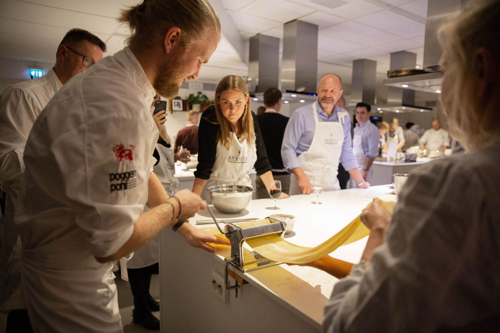 En kock gör egen pasta och personer kollar på