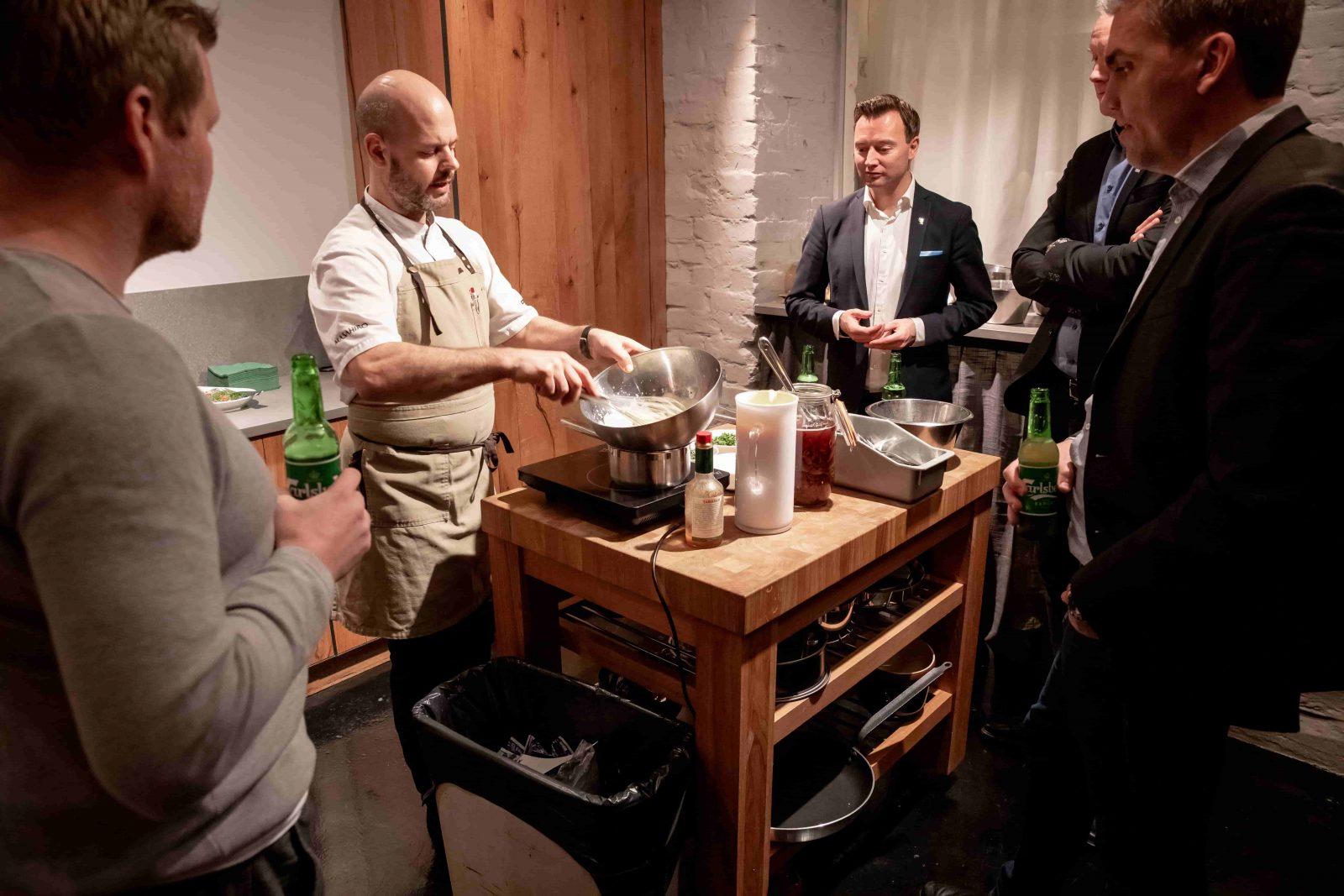 Fyra män kollar på när en annan man vispar en smet